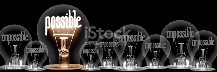 Large group of shining and dimmed light bulbs with fibers in a shape of Impossible and Possible words isolated on black background; concept of Motivation, Success and Change