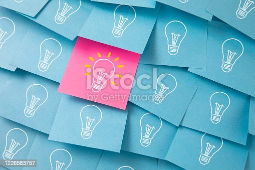 Many light bulbs drawn on blue and pink adhesive notes