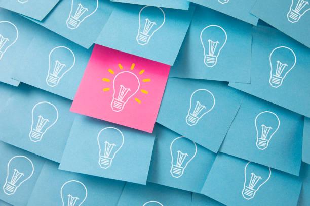 glühbirnen gezeichnet auf bunten haftnotizen - idee stock-fotos und bilder
