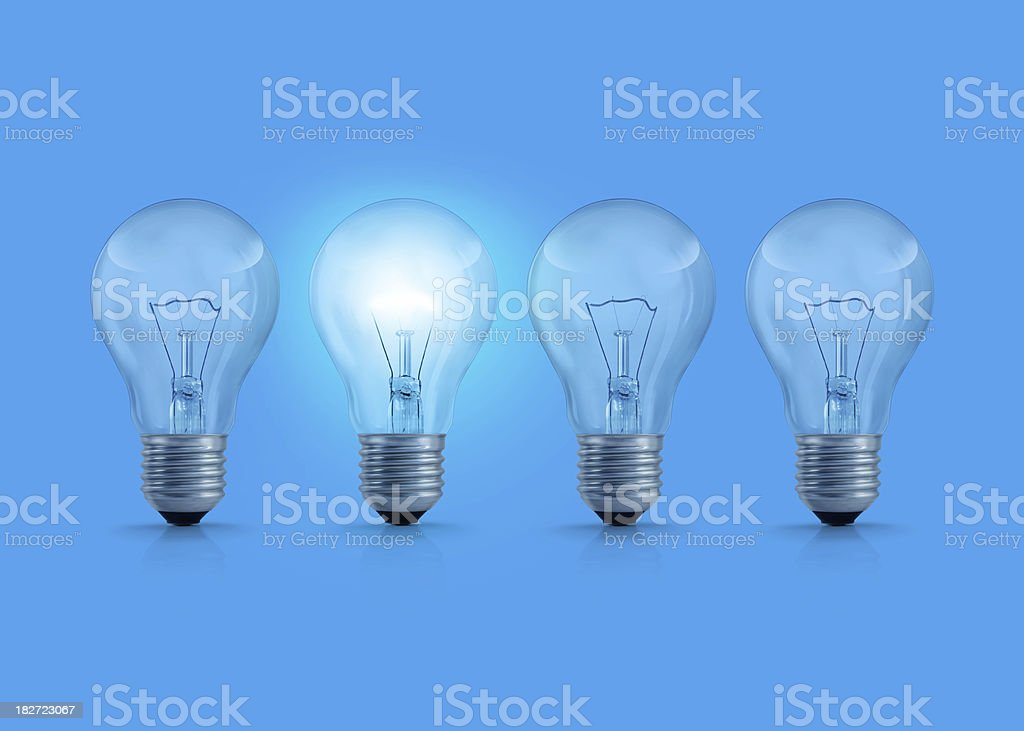 Four light bulbs on blue background. One of them is glowing.