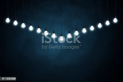 istock Light bulbs on dark blue background 911305398