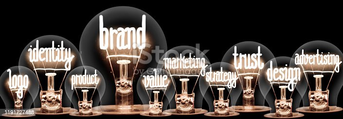 Group of light bulbs with shining fibers in a shape of Brand, Identity, Value, Marketing and Trust concept related words isolated on black background; horizontal composition