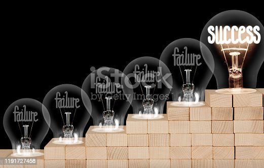 Group of shining and dimmed light bulbs on wooden block ladder with fibers in a shape of Failure and Success concept words isolated on black background.