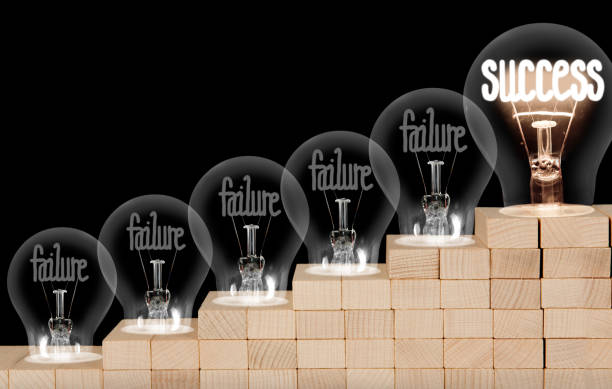 Light Bulbs with Failure and Success Concept Group of shining and dimmed light bulbs on wooden block ladder with fibers in a shape of Failure and Success concept words isolated on black background. failure stock pictures, royalty-free photos & images