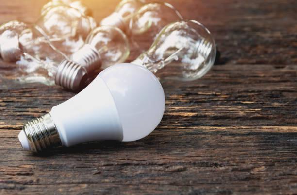 ampoules avec brillant sur fond de table en bois. idée, créativité et économies d'énergie avec les ampoules concept. - efficacité énergétique photos et images de collection