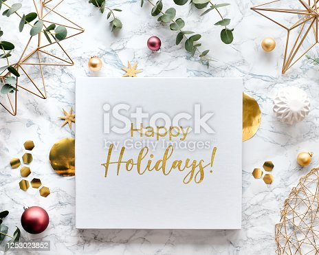 Light Christmas frame with fresh eucalyptus twigs and golden geometric decorations - hexagons, trinkets and wire shapes. Flat lay on white marble background with text Happy Holidays on canvas