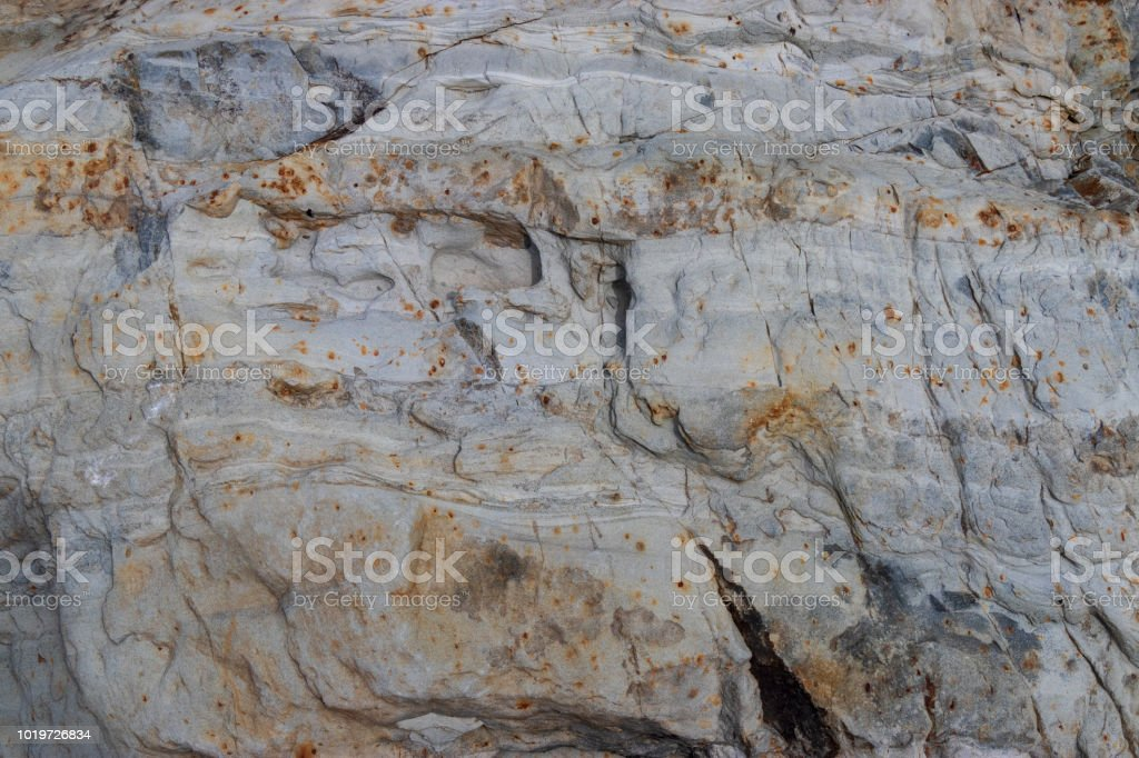 A light colored outcrop of rock with rust speckles. stock photo