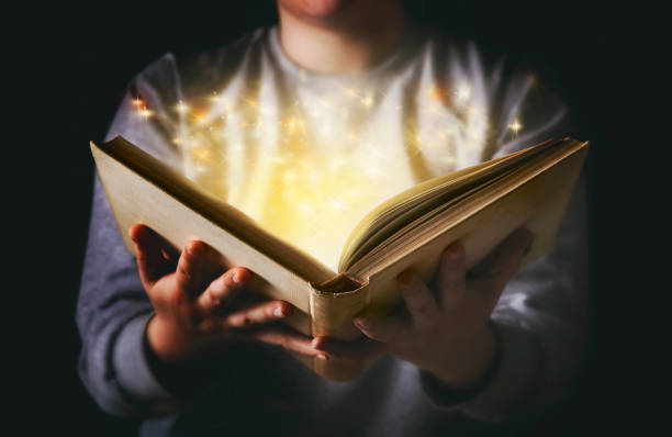 light coming from book in woman's hands in gesture of giving - fairy tale stock pictures, royalty-free photos & images