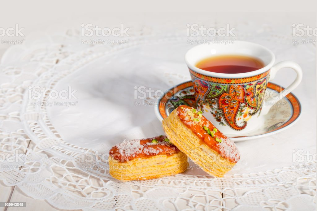 Light Crunchy Puff Layered Pastry Garnished With Pistachios & Coconut Flakes And A Traditional Cup Of Tea Popular Persian Sweets In Iran Called Zaboon Or Zaban stock photo