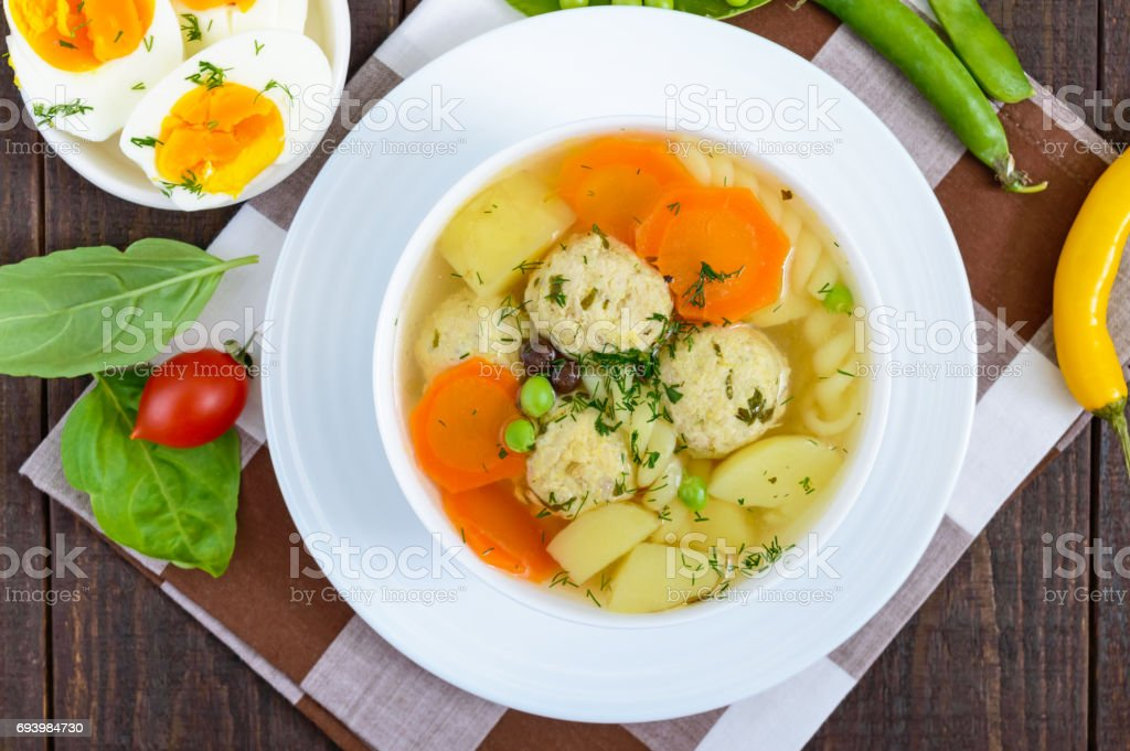 Light dietary soup with meat balls, vegetables, fusilli and boiled eggs on a dark wooden table. Useful lunch. The top view stock photo