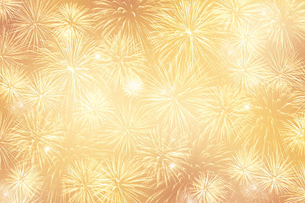 light golden festive background with lots of fireworks - new year стоковые фото и изображения