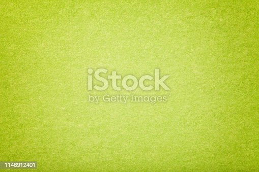 Light green matte background of suede fabric, closeup. Velvet texture of seamless olive woolen felt. Gradient backdrop