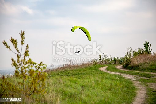 Light green paraglider descends from the mountain. Green grass and a sandy road in the foreground. Horizontal orientation. High quality photo.