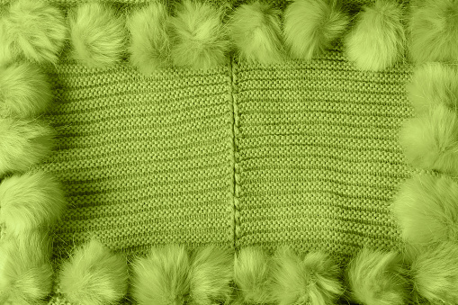 Light green winter textile background with copy space and a frame with fluffy pompoms
