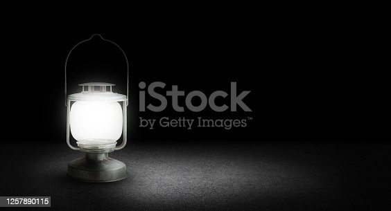 Abstract low key image of Light growing from Old metal vintage lantern on concrete floor in dark background.