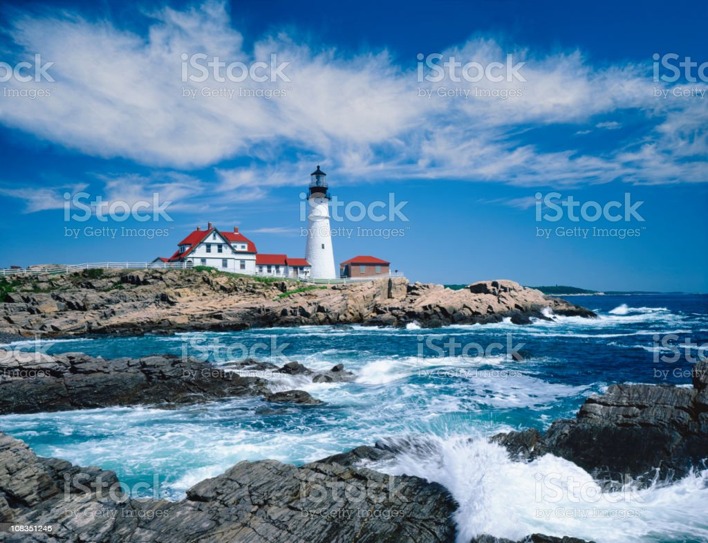 A light house on a rocky cliff in Portland royalty-free stock photo