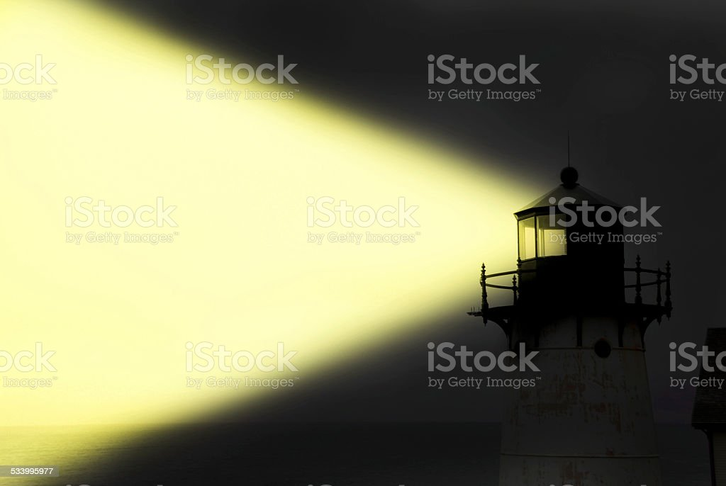 Light House Shining Yellow Light Beam At Night. stock photo