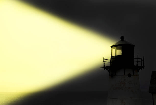 Light House Shining Yellow Light Beam At Night. Light house shining yellow light at night with copy space. beacon stock pictures, royalty-free photos & images