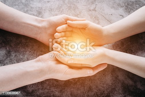 974882202 istock photo Light in young family hands offering help, protection and support symbol. Sharing hope concept 1133638967