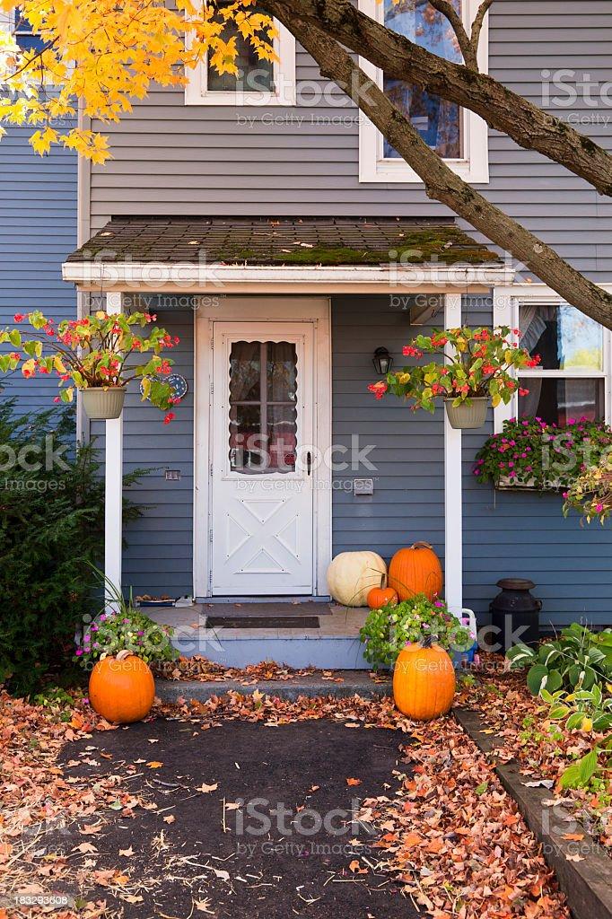 Light indigo colored house with white door and autumn decor stock photo