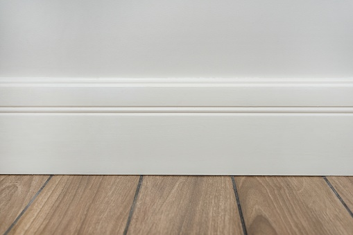 Interior concept. Light matte wall, white baseboard and tiles immitating hardwood flooring