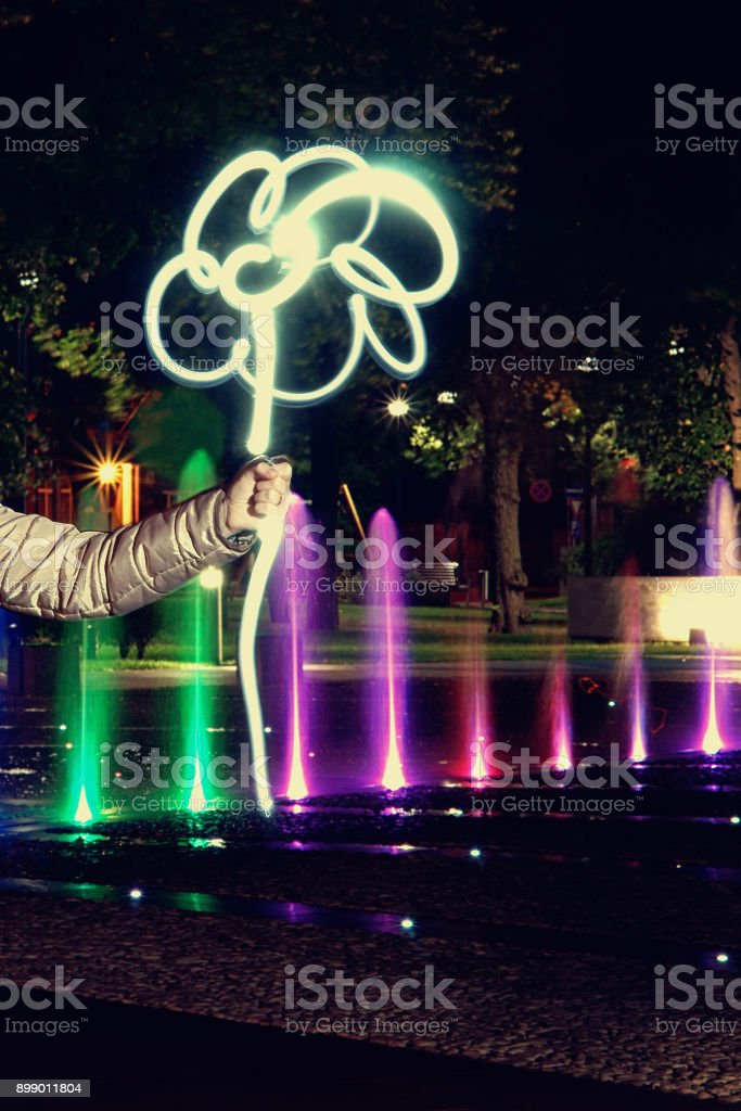 Light painting a flower at night in hand stock photo