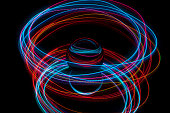 Abstract light painting circling around a crystal ball on a black background.