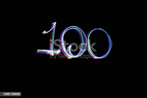 Light painting number 100 with black background. Coloured LED lights used to write numbers.