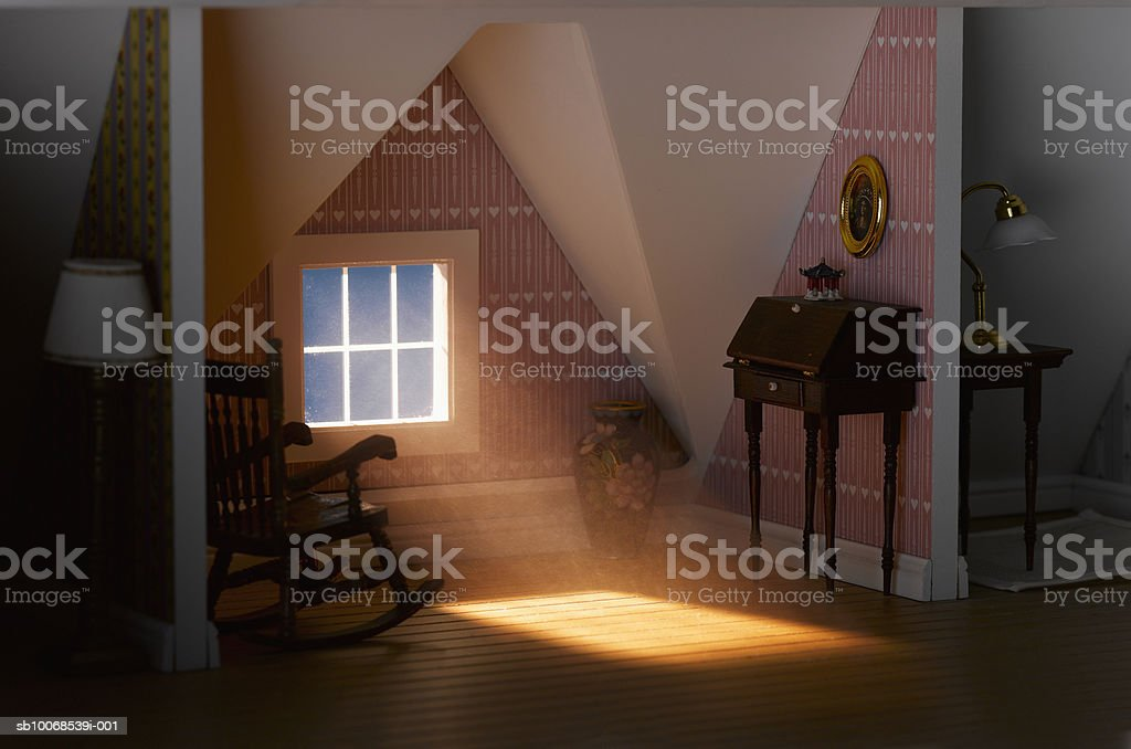 Light passing through attic window of model house, close-up royalty-free stock photo