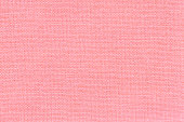 Light pink background from a textile material with wicker pattern, closeup.
