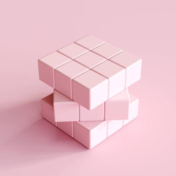cube rose clair rubik's sur fond rose clair. idée concept minimal - monochrome image teintée photos et images de collection