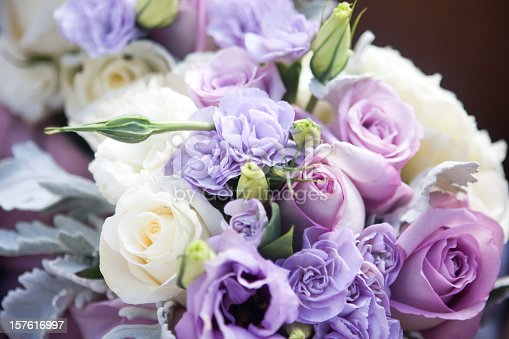 A brides purple and white rose bouquet.