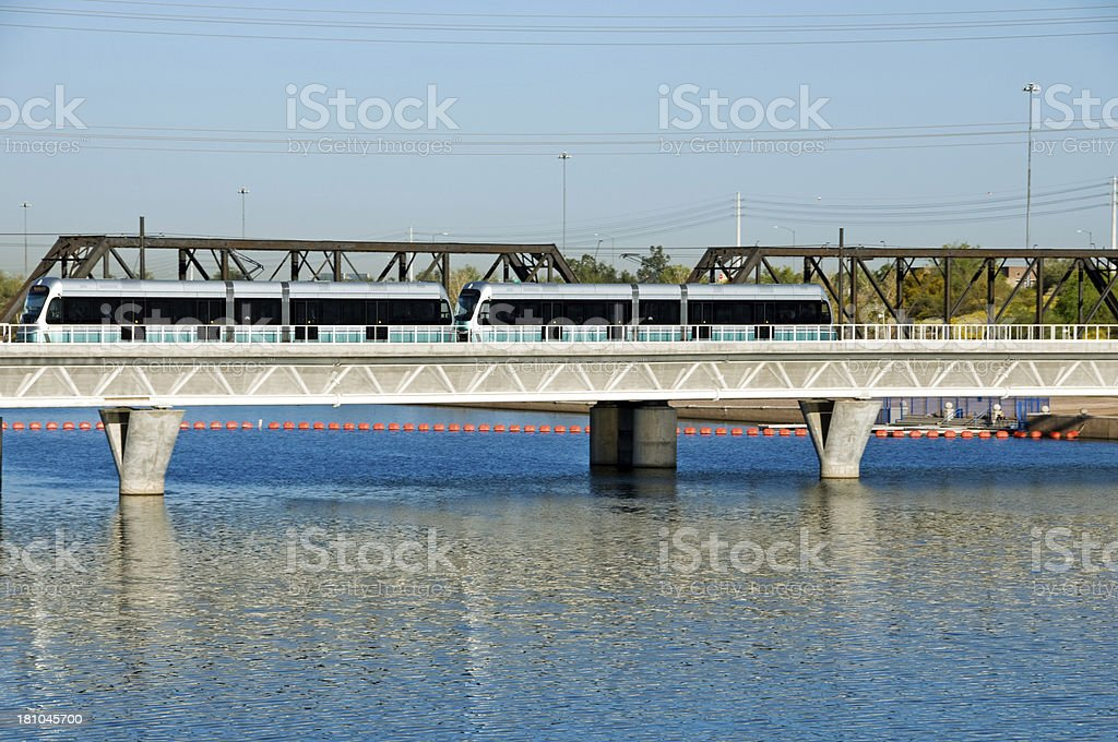 Light rail train crossing man-made lake in Tempe AZ royalty-free stock photo
