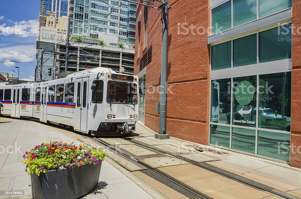 Light rail train traveling through a sun filled city stock photo