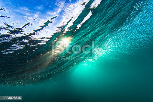 istock Light rays from the sun penetrating through a wave in a clear blue underwater scene 1223028340