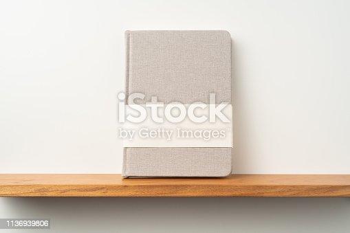 istock light red fabric notebook stand on bookshelf 1136939806