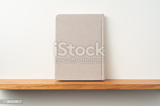 istock light red fabric notebook stand on bookshelf 1136939822