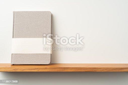 1221251713 istock photo light red fabric notebook stand on bookshelf 1138012668
