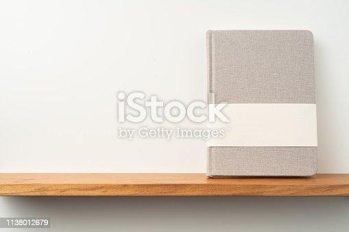 istock light red fabric notebook stand on bookshelf 1138012679