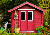 istock A light red small shed, gardenhouse, with some garden tools around it 1187223571