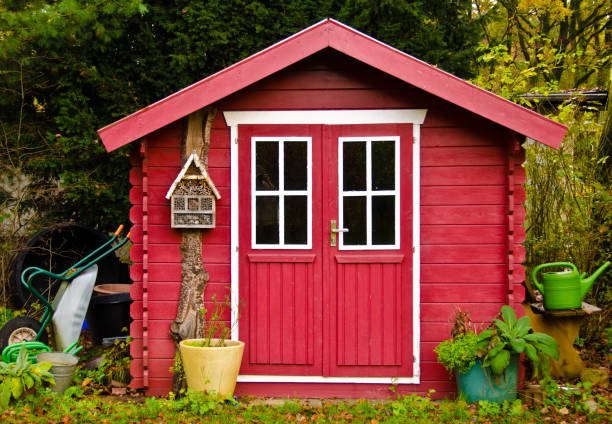 A light red small shed, gardenhouse, with some garden tools around it A light red small shed, gardenhouse, with some garden tools around it shed stock pictures, royalty-free photos & images