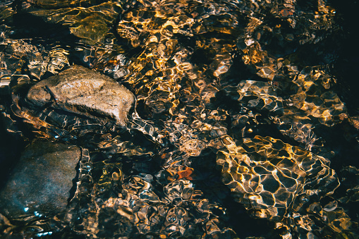 Light reflections in the water of a river with some rocks under water.