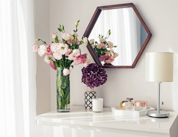 Light room with mirrow, flowers, night lamp and other objects stock photo