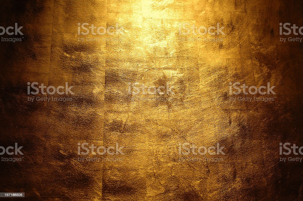 Light shining above a golden wall stock photo