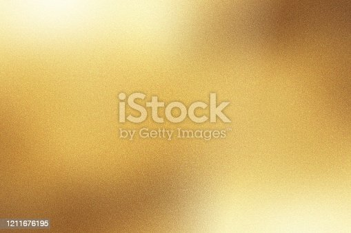 Light shining down on gold foil metal wall with copy space, abstract background