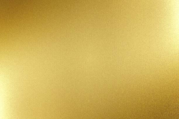licht schijnt op gold metal board, abstracte textuur achtergrond - messing stockfoto's en -beelden