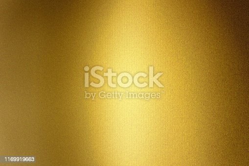 Light shining on gold metallic foil wall, abstract texture background