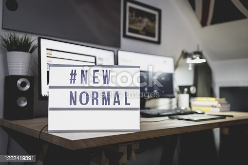 Light signs with text hashtag #NEW NORMAL on the working desk. Work from home. New normal concept. Social distancing.