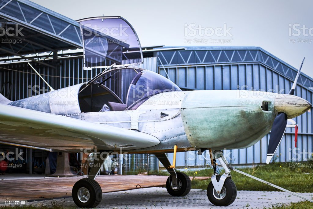 Light single-engine aircraft in the summer before the storage hangar. stock photo