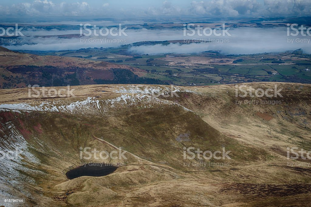 light snow topped welsh mountain with lake and mist stock photo